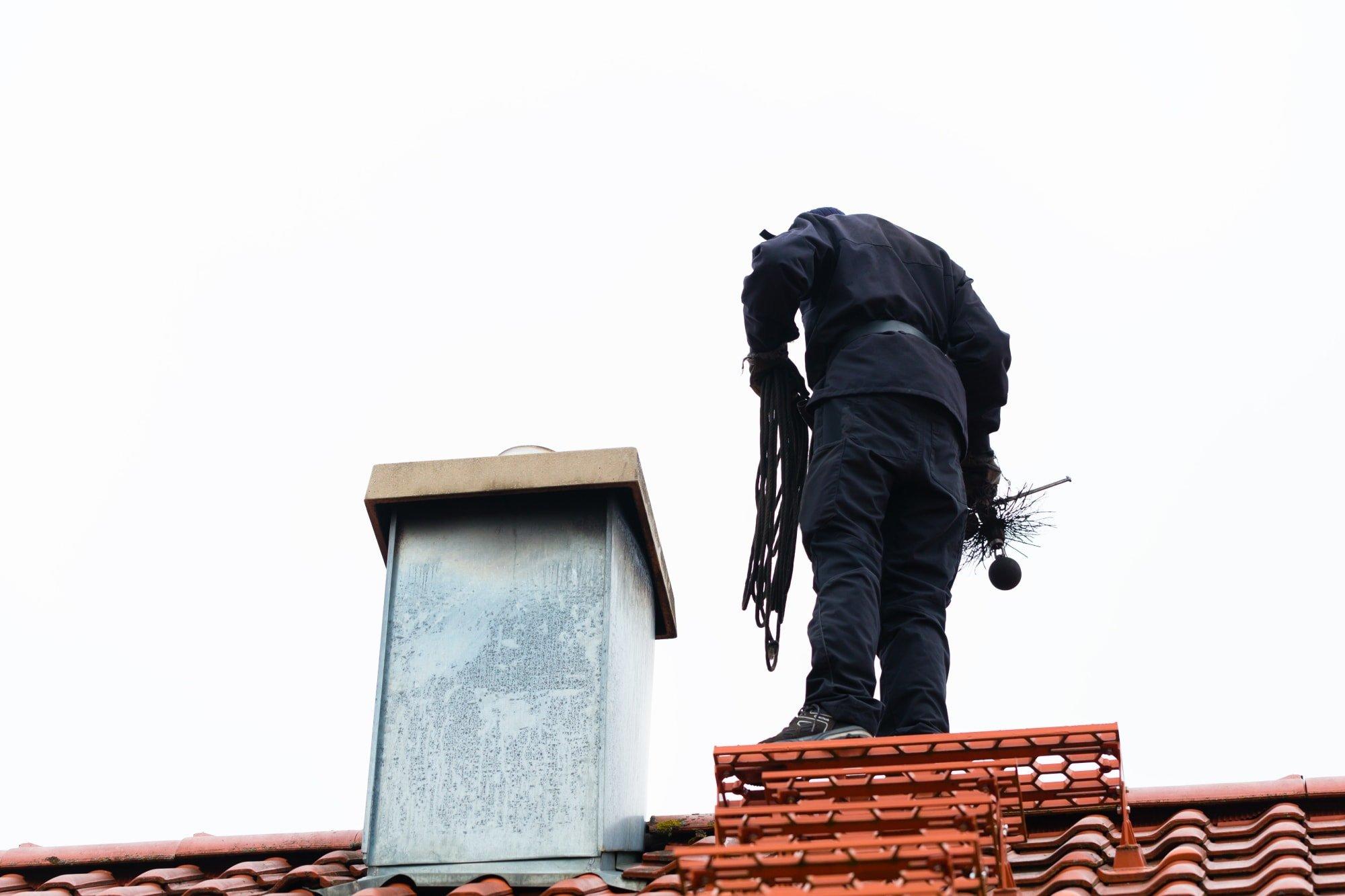 Kominík při práci na střeše