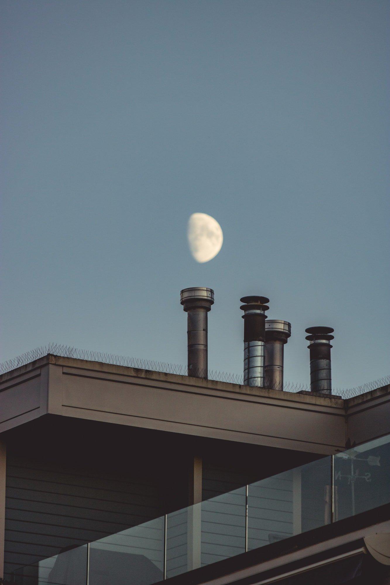 Komíny na střeše měsíc v pozadí